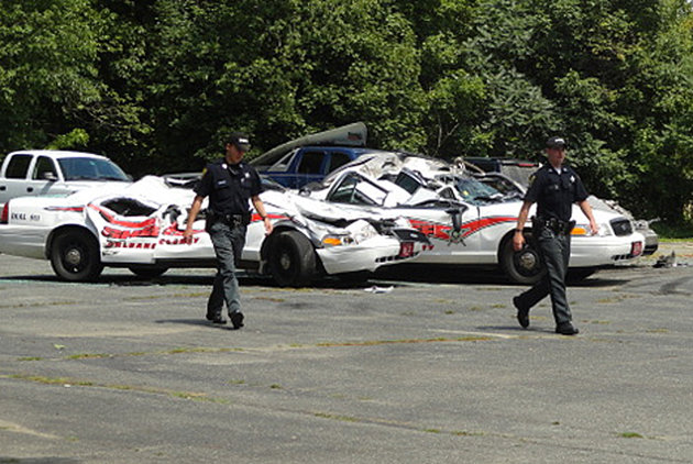 Sheriff officers walk past crushed cruisers at the Orleans County Sheriff's Department in Newport, Vt.